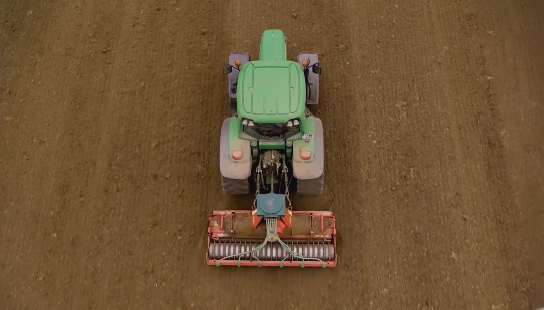 Tractor reseeding field in spring